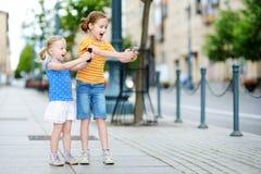 Två gulliga lilla systrar som spelar den utomhus- mobilleken på deras smarta telefoner Royaltyfri Foto