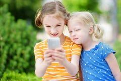 Två gulliga lilla systrar som spelar den utomhus- mobilleken på deras smarta telefoner Royaltyfri Bild