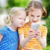 Två gulliga lilla systrar som spelar den utomhus- mobilleken på deras smarta telefoner Arkivbild