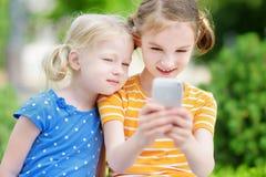 Två gulliga lilla systrar som spelar den utomhus- mobilleken på deras smarta telefoner Royaltyfri Fotografi
