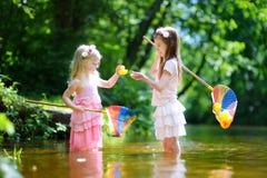 Två gulliga lilla systrar som spelar i en flod som fångar rubber änder med deras, skopa-förtjänar Fotografering för Bildbyråer