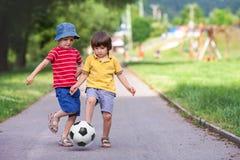 Två gulliga lilla ungar som spelar fotboll tillsammans, sommartid Royaltyfri Fotografi