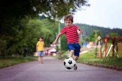 Två gulliga lilla ungar som spelar fotboll tillsammans, sommartid Arkivfoto