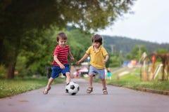 Två gulliga lilla ungar som spelar fotboll tillsammans, sommartid Royaltyfri Bild
