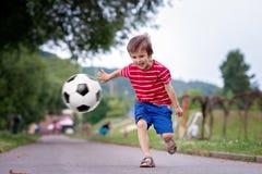 Två gulliga lilla ungar som spelar fotboll tillsammans, sommartid Arkivfoton