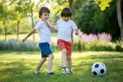 Två gulliga lilla ungar som spelar fotboll tillsammans, sommartid chi Arkivbild