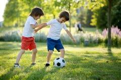 Två gulliga lilla ungar som spelar fotboll tillsammans, sommartid chi Arkivfoto