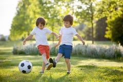 Två gulliga lilla ungar som spelar fotboll tillsammans, sommartid chi Fotografering för Bildbyråer