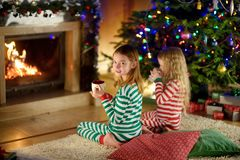Två gulliga lyckliga flickor som har varm choklad vid en spis i en hemtrevlig mörk vardagsrum på julhelgdagsafton royaltyfria foton