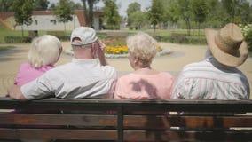 Två gulliga mogna par som sitter på bänken och tillsammans talar Moget folk som vilar det fria gladlynt pension?r arkivfilmer