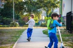Två gulliga pojkar, konkurrerar i ridningsparkcyklar som är utomhus- i parkera, fotografering för bildbyråer