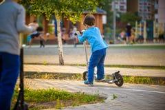 Två gulliga pojkar, konkurrerar i ridningsparkcyklar som är utomhus- i parkera, arkivfoton