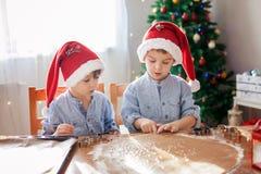 Två gulliga pojkar med den santa hatten som hemma förbereder kakor, Christm Royaltyfria Foton