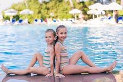 Två gulliga små flickor i simbassäng Arkivfoto