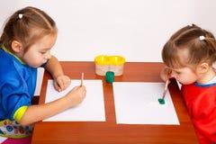 Två gulliga små flickor målar med gouache Royaltyfri Fotografi