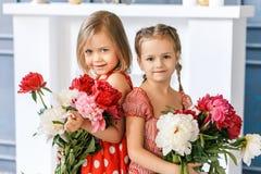Två gulliga små flickor med pioner Två härliga vänner som har gyckel, att krama och att le royaltyfri foto