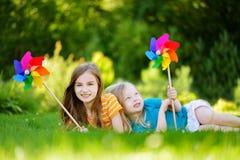 Två gulliga små flickor som rymmer färgrika leksaksmå solar på solig sommardag Arkivbild