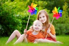 Två gulliga små flickor som rymmer färgrika leksaksmå solar på solig sommardag Royaltyfri Foto