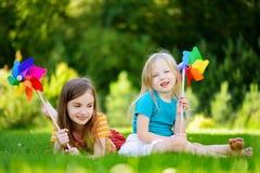 Två gulliga små flickor som rymmer färgrika leksaksmå solar på solig sommardag Arkivfoton