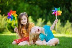 Två gulliga små flickor som rymmer färgrika leksaksmå solar på varm och sommardag Arkivfoto