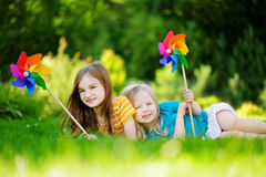 Två gulliga små flickor som rymmer färgrika leksaksmå solar på varm och sommardag Arkivfoton