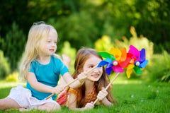 Två gulliga små flickor som rymmer färgrika leksaksmå solar på varm och sommardag Royaltyfria Bilder