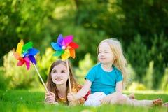 Två gulliga små flickor som rymmer färgrika leksaksmå solar på varm och sommardag Arkivbilder