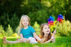 Två gulliga små flickor som rymmer färgrika leksaksmå solar på varm och sommardag Royaltyfri Fotografi