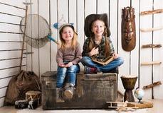 Två gulliga små flickor som sitter på stor träbröstkorg royaltyfri fotografi