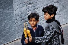 Två gulliga svart-haired svartmuskiga azerbajdzjanska pojkar som spelar, ler och äter chiper på en pinne royaltyfri bild