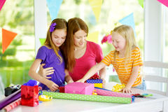 Två gulliga systrar och deras unga moder som slår in gåvor i färgrikt inpackningspapper Royaltyfria Bilder