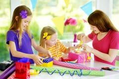 Två gulliga systrar och deras unga moder som slår in gåvor i färgrikt inpackningspapper Arkivfoton