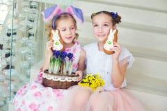 Två gulliga systrar som inomhus sitter med kaninöron, blommor och gi Arkivbilder