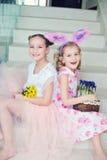Två gulliga systrar som inomhus sitter med kaninöron, blommor och gi Arkivfoto
