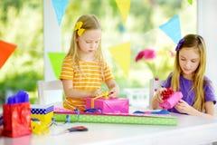 Två gulliga systrar som slår in gåvor i färgrikt inpackningspapper Royaltyfria Foton