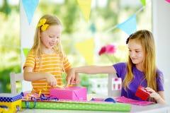 Två gulliga systrar som slår in gåvor i färgrikt inpackningspapper Royaltyfri Bild