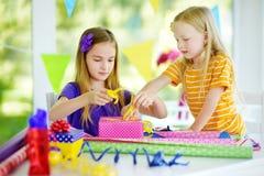 Två gulliga systrar som slår in gåvor i färgrikt inpackningspapper Arkivfoto