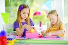 Två gulliga systrar som slår in gåvor i färgrikt inpackningspapper Fotografering för Bildbyråer