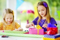Två gulliga systrar som slår in gåvor i färgrikt inpackningspapper Arkivfoton