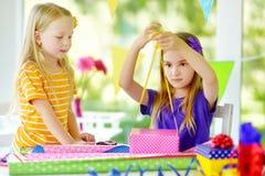 Två gulliga systrar som slår in gåvor i färgrikt inpackningspapper Arkivbilder