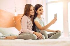 Två gulliga systrar som tar selfies på säng arkivfoton