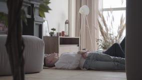 Två gulliga tonåriga pojkar som ligger på golvet i barns rum som talar och att dela och att meddela Begrepp av broderförälskelse  arkivfilmer