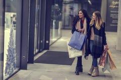 Två gulliga tonårs- unga kvinnor som shoppar på en kall vinterafton, medan rymma stora shoppingpåsar Arkivbild