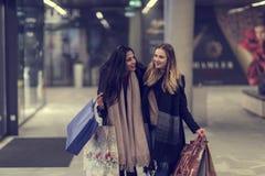 Två gulliga tonårs- unga kvinnor som shoppar på en kall vinterafton, medan rymma stora shoppingpåsar Royaltyfri Bild