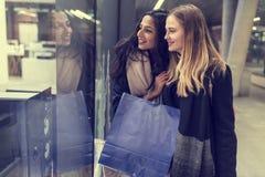 Två gulliga tonårs- unga kvinnor som shoppar på en kall vinterafton, medan rymma stora shoppingpåsar Royaltyfri Foto
