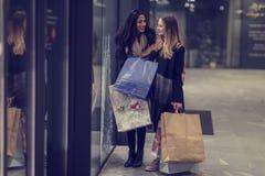 Två gulliga tonårs- unga kvinnor som shoppar på en kall vinterafton, medan rymma stora shoppingpåsar Royaltyfria Bilder