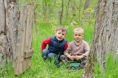 Två gulliga unga pojkar som spelar i skogsmark Arkivfoton