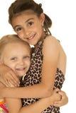 Två gulliga unga systrar som kramar sig bärande baddräkter Royaltyfri Fotografi