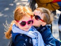 Två gulliga ungar med solexponeringsglas kyssa för pojkeflicka royaltyfri bild