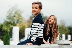 Två gulliga ungar sitter på räcket Marmor-sten springbrunn royaltyfria bilder
